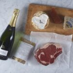Rib of beef next to a heart shaped cheese, bottle of champagne, steak sauce and crackers